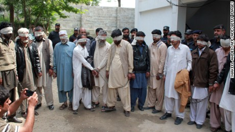 "Pakistani police escort blindfolded suspects accused of killing and setting fire to a woman as they appear at a court in Abbottabad on May 5, 2016.   A Pakistani woman was drugged, strangled and then her body set ablaze because she helped her friend elope, police said May 5, announcing the arrest of 14 people in a twist on the grim practice of ""honor killings"". / AFP PHOTO / SHAKEEL AHMEDSHAKEEL AHMED/AFP/Getty Images"