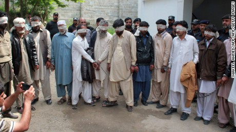 """Pakistani police escort blindfolded suspects accused of killing and setting fire to a woman as they appear at a court in Abbottabad on May 5, 2016.   A Pakistani woman was drugged, strangled and then her body set ablaze because she helped her friend elope, police said May 5, announcing the arrest of 14 people in a twist on the grim practice of """"honour killings"""". / AFP PHOTO / SHAKEEL AHMEDSHAKEEL AHMED/AFP/Getty Images"""