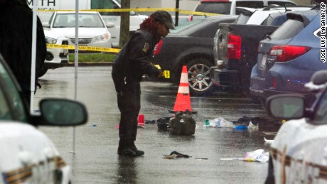 A Montgomery County, Md. Police officer marks evidence after a shooting outside Westfield Montgomery Mall parking lot in Bethesda, Md., Friday, May 6, 2016. Police in Maryland sat three people were hurt after the shooting. (AP Photo/Jose Luis Magana)