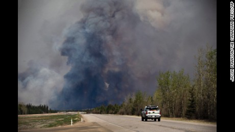 A truck drives toward a wildfire in Fort McMurray, Alberta, on Friday, May 6, 2016. More than 80,000 people have left Fort McMurray in the heart of Canada oil sands, where the fire has torched over 1,000 homes and other buildings. (Jason Franson /The Canadian Press via AP) MANDATORY CREDIT
