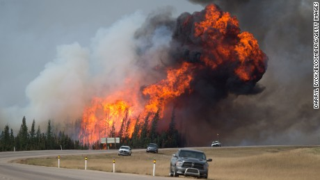 A wildfire burns behind abandoned vehicles on the Alberta Highway 63 near Fort McMurray, Alberta, Canada, on Saturday, May 7, 2016. Wildfires ravaging the center of Canada's oil patch in northern Alberta may double in size as warm temperatures and swirling winds push the inferno in the direction of major oil-sands operations. Photographer: Darryl Dyck/Bloomberg via Getty Images
