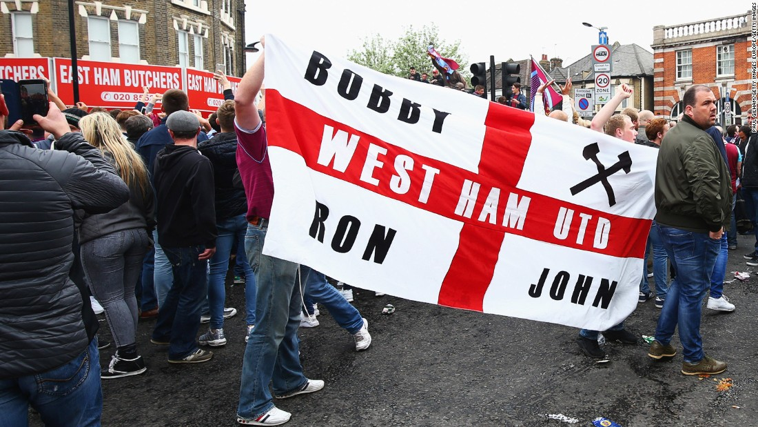 West Ham fans display a flag honoring three of the club's greatest names: former captain Bobby Moore and ex-managers Ron Greenwood and John Lyall.