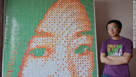 SHENYANG, CHINA - MAY 10: (CHINA OUT) 27-year-old rubik's cube lover Tong Ao'nan and self-made portrait of his sweetheart on May 10, 2016 in Shenyang, Liaoning Province of China. Tong Ao'nan, a rubik's cube lover decided to assemble rubik's cubes into portrait of a girl he loved as he viewed jigsaws from rubik's cubes on internet. He created a 2.6 meters high and 1.37 meters tall portrait with 840 rubik's cubes to declare to that girl, but unluckily he was rejected.  (Photo by VCG/Getty Images)