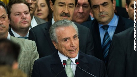 """Brazilian acting president Michel Temer (C) speaks during his new ministers' inauguration ceremony at Planalto palace in Brasilia, on May 12, 2016.  Temer said Thursday his new cabinet must work to restore the country's """"credibility,"""" in his first address after assuming power from suspended predecessor Dilma Rousseff pending her impeachment trial. / AFP / ANDRESSA ANHOLETE        (Photo credit should read ANDRESSA ANHOLETE/AFP/Getty Images)"""