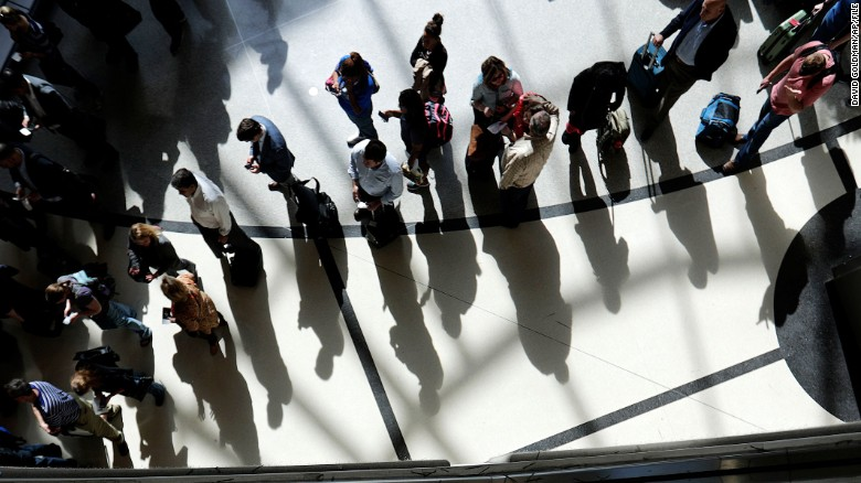 Passengers are reflected in glass as they line up to go through a security checkpoint under the atrium of the domestic passenger terminal at Hartsfield-Jackson Atlanta International Airport on Thursday, March 10, 2016, in Atlanta. On Thursday, officials announced a $6 billion expansion and renovation project at the world's busiest airport during the next 20 years. (AP Photo/David Goldman)