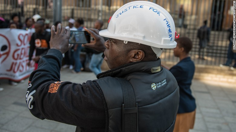 A supporter of miners films a protest outside court in Johannesburg.
