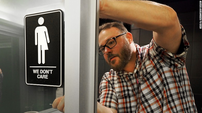 DURHAM, NC - MAY 10:  Museum manager Jeff Bell adheres informative backing to gender neutral signs in the 21C Museum Hotel public restrooms on May 10, 2016 in Durham, North Carolina.  Debate over transgender bathroom access spreads nationwide as the U.S. Department of Justice countersues North Carolina Governor Pat McCrory from enforcing the provisions of House Bill 2 that dictate what bathrooms transgender individuals can use.  (Photo by Sara D. Davis/Getty Images)