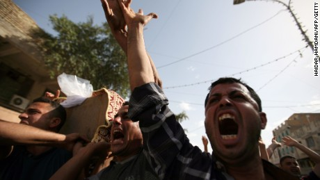 Iraqis shout as they carry the coffin of a victim following a twin suicide bombing attack, claimed by the Islamic State (IS) group, in the southern Iraqi city of Samawah, situated deep in Iraq's Shiite heartland, on May 1, 2016.      / AFP / HAIDAR HAMDANI        (Photo credit should read HAIDAR HAMDANI/AFP/Getty Images)
