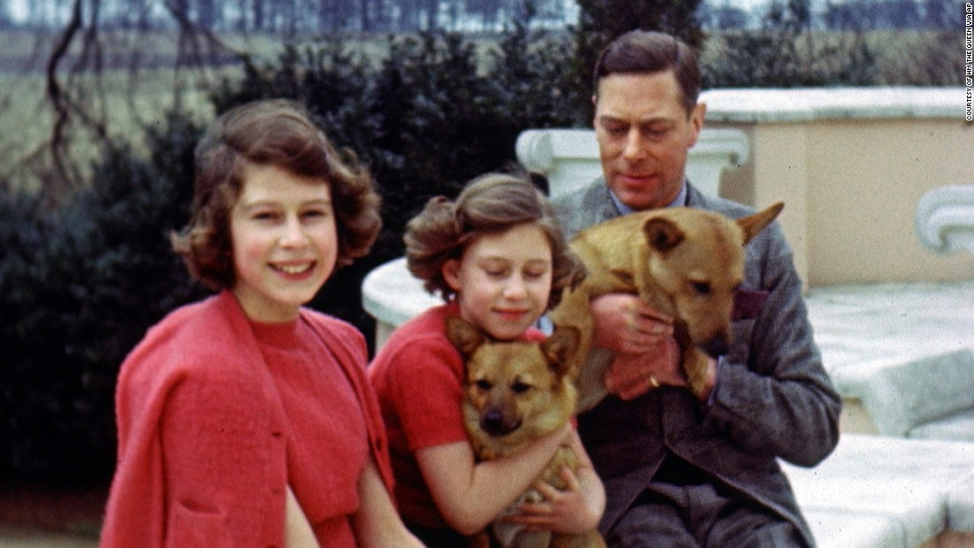 Princess Elizabeth, center, sits with her parents and two dogs in an undated photos.