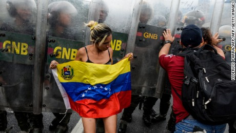 Members of the opposition of Venezuelan President Nicolas Maduro clash with riot police during a demonstration in Caracas on May 11, 2016.  With helmets, shields and bulletproof, military and Venezuelan police vests prevented Wednesday the advance of thousands of opponents who tried to reach the headquarters of the National Electoral Council (CNE), to demand accelerate the process of a recall referendum against President Nicolas Maduro. / AFP / FEDERICO PARRA        (Photo credit should read FEDERICO PARRA/AFP/Getty Images)