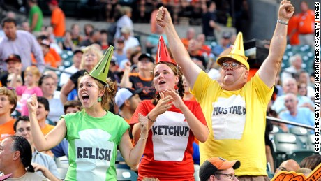 BALTIMORE, MD - AUGUST 07:  (L to R) Susan Handley, Kaity Handley and John Handley cheer during the video board condiment race during the game between the Seattle Mariners and the Baltimore Orioles at Oriole Park at Camden Yards on August 7, 2012 in Baltimore, Maryland.  (Photo by Greg Fiume/Getty Images)