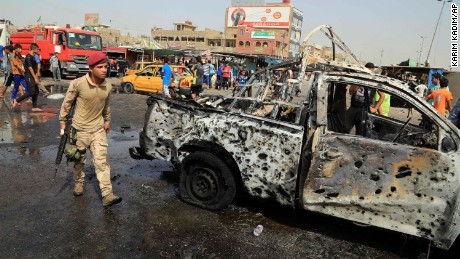 Security forces and citizens inspect the scene after a suicide car bomb hit a crowded outdoor market in Baghdad's eastern Shiite neighborhood of Sadr City, Iraq, Tuesday, May 17, 2016. A wave of bombings struck outdoor markets in Shiite-dominated neighborhoods of Baghdad on Tuesday, killing and wounding dozens of civilians, officials said, the latest in deadly militant attacks far from the front lines in the country's north and west where Iraqi forces are battling the Islamic State group. (AP Photo/Karim Kadim)