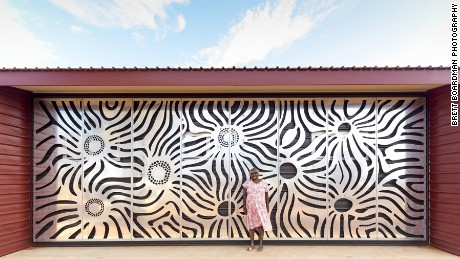 One of the community's artists, Mrs Ward, stands in front of the art screen she designed. Aside from their artistic beauty, the screens shade the building from the north, protecting it from the region's intense desert heat.