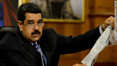 """Venezuelan President Nicolas Maduro reads a newspaper article during a press conference at the Miraflores presidential palace in Caracas on May 17, 2016. The army in crisis-hit Venezuela has to choose whether it is """"with the constitution or with (President Nicolas) Maduro,"""" opposition leader Henrique Capriles said Tuesday. / AFP / FEDERICO PARRA        (Photo credit should read FEDERICO PARRA/AFP/Getty Images)"""