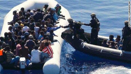 German Navy sailors surround a boat with more than 100 migrants near the German combat supply ship 'Frankfurt am Main' during EUNAVFOR Med, also known as Operation Sophia, in the Mediterranean Sea off the coast of Libya, Tuesday, March 29, 2016. (AP Photo/Matthias Schrader)