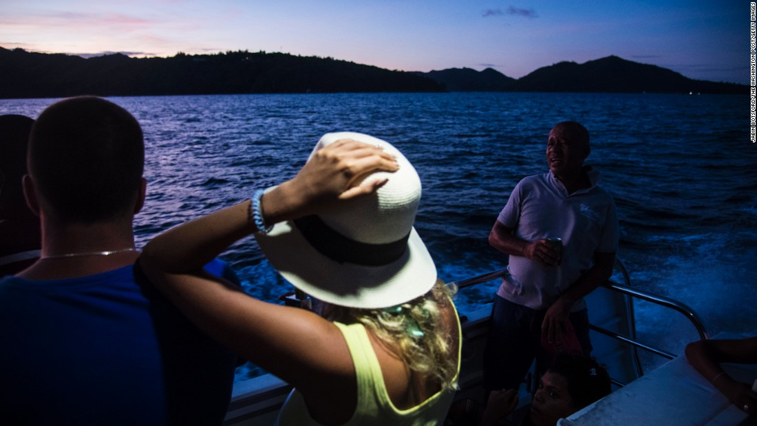 Ferry passengers watch the sun set as they leave the island of Praslin in the Seychelles. Praslin's <a href=