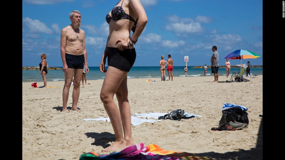 Beachgoers stand still on May 11 as they observe two minutes of silence to mark Israel's annual Memorial Day for fallen soldiers.