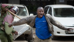 An opposition supporter yells out as he is beaten with a wooden club by riot police while trying to flee, during a protest in downtown Nairobi, Kenya Monday, May 16, 2016. Kenyan police have tear-gassed and beaten opposition supporters during a protest demanding the disbandment of the electoral authority over alleged bias and corruption. (AP Photo/Ben Curtis)