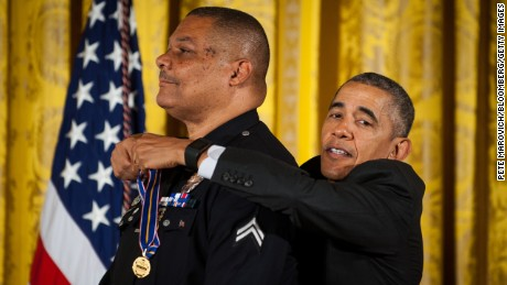 U.S. President Barack Obama, right, awards the Medal of Valor to Officer Donald Thompson, with the Los Angeles Police Department, CA, for courageous action to save an accident victim, during a ceremony in the East Room of the White House in Washington, D.C., U.S., on Monday, May 16, 2016. While off duty, Officer Thompson traversed two freeway dividers and endured first- and second-degree burns while pulling an unconscious man to safety from a car moments before it became engulfed in flames. According to the White House, the Medal of Valor is awarded to public safety officers who have exhibited exceptional courage, regardless of personal safety, in the attempt to save or protect others from harm. Photographer: Pete Marovich/Bloomberg via Getty Images