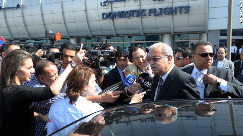 Egyptian Prime Minister Sherif Ismail talks to reporters at Cairo International Airport.