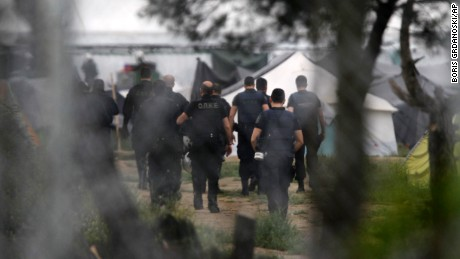 Greek policemen walk at a makeshift refugee camp at the Greek-Macedonian border near the northern village of Idomeni, Tuesday, May 24, 2016. Greek authorities have begun an operation to gradually evacuate the country's largest informal refugee camp of Idomeni, located on the Greek-Macedonian border, where more than an estimated 8,400 people have been living for months. (AP Photo/Boris Grdanoski)