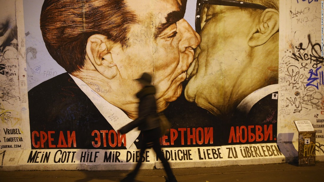"""The mural is a play on a famous work of art on the Berlin wall depicting Soviet leader Leonid Brezhnev and East German leader Erich Honecker sharing a kiss. The message below reads: """"My God, help me survive this deadly love."""""""