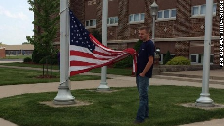 18-year-old Cole Dotson of Continental, Ohio holds the American Flag until help arrives.
