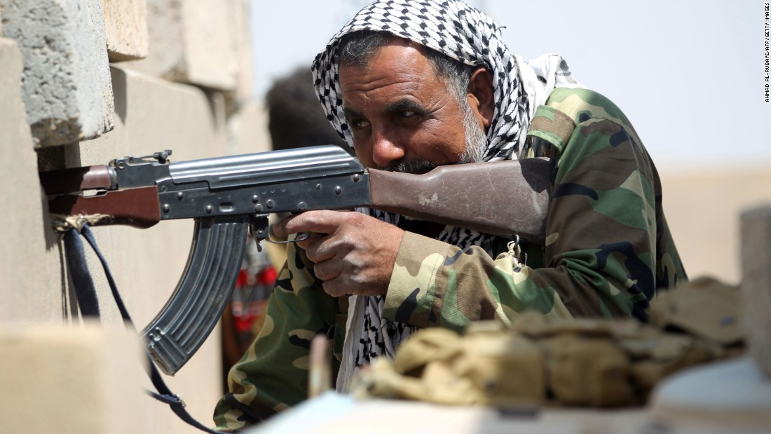 A pro-government fighter holds position in the village of al-Shahabi, east of Falluja, on Tuesday, May 24.