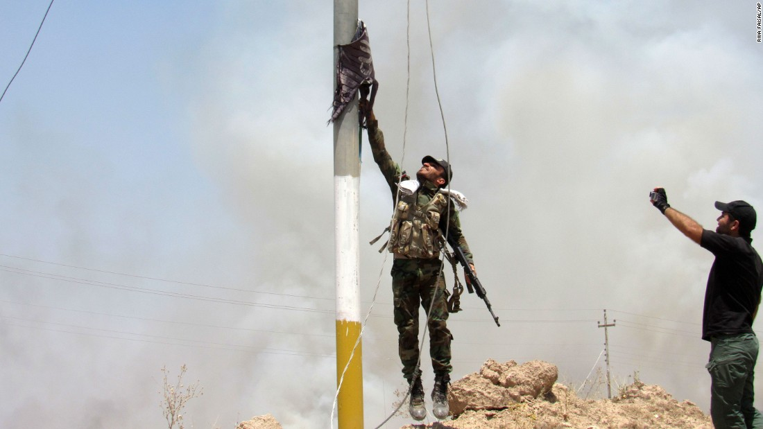 A fighter with the Badr Brigades, a Shiite militia, takes an ISIS flag down outside Falluja on May 23.