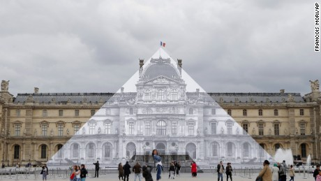 Tourists walk around theJR project at the Louvre Pyramid in Paris, Tuesday, May 24, 2016. For his latest bold project, street artist JR is creating an eye-tricking installation at the Louvre Museum that makes it seem as if the huge glass pyramid at the heart of the courtyard has disappeared. (AP Photo/Francois Mori)