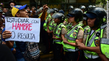 """A protester holds a sign reading """"studying when you're hungry doesn't work"""", as police stand guard while public university students in Venezuela protest the policies of the government of President Nicolas Maduro in Caracas on May 26, 2016. / AFP / RONALDO SCHEMIDT        (Photo credit should read RONALDO SCHEMIDT/AFP/Getty Images)"""