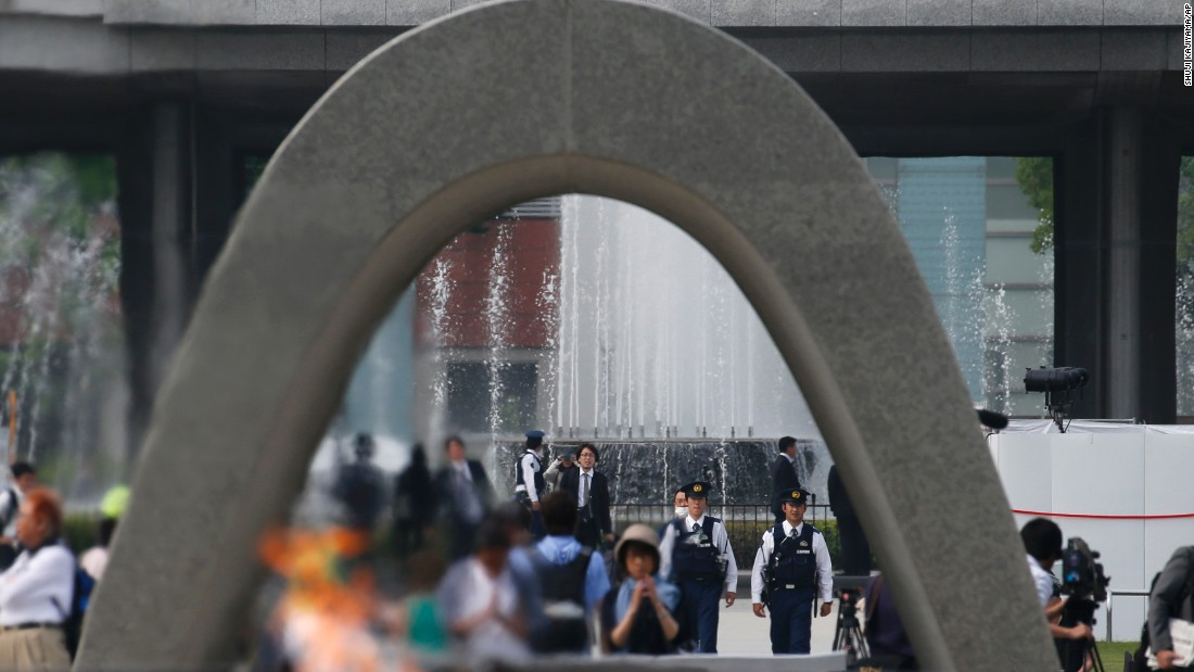 Police officers, seen through the cenotaph, patrol at Hiroshima Peace Memorial Park in Hiroshima.