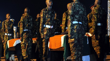 Kenyan soldiers stand over caskets bearing the remains of four comrades killed in Somalia