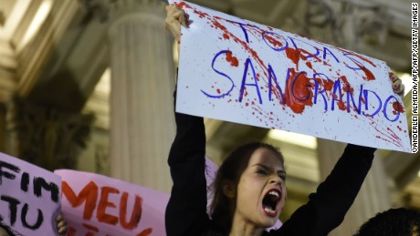 Brazilians protest in front of the Legislative Assembly of Rio de Janeiro (ALERJ) on May 27, 2016, against a gang-rape of a 16-year-old girl.  Brazilian police on Friday were investigating the gang-rape of a 16-year-old girl whose attackers boasted about it by posting an online video of her that has horrified the country. Online social networks erupted with outrage over the video posted on Wednesday featuring the girl naked on a bed and the apparent rapists bragging that she had been raped by more than 30 men. / AFP / VANDERLEI ALMEIDA        (Photo credit should read VANDERLEI ALMEIDA/AFP/Getty Images)