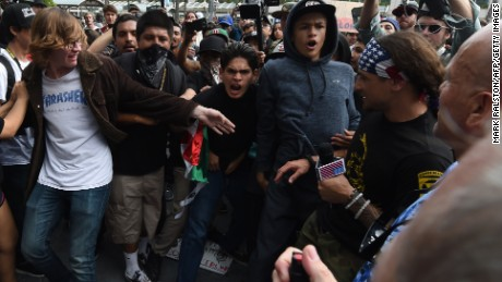Anti-Donald Trump protesters are threatened with pepper spray by a Trump supporter outside Republican presidential candidate Donald Trump's election rally event in San Diego, California, on May 27, 2016.