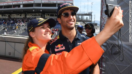 Infiniti Red Bull Racing's Australian driver Daniel Ricciardo poses for a photograph with a track marshall during the qualifying session at the at the Monaco street circuit, on May 28, 2016 in Monaco, one day ahead of the Monaco Formula 1 Grand Prix.  / AFP / PASCAL GUYOT        (Photo credit should read PASCAL GUYOT/AFP/Getty Images)