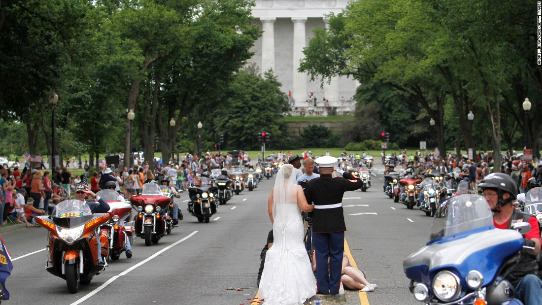 Retired Marine Staff Sgt. Tim Chambers and his new wife, Lorraine, salute riders during the Rolling Thunder event.