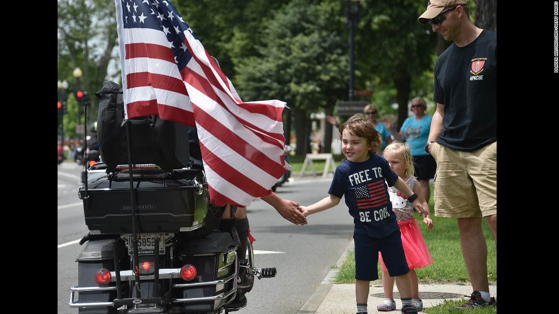 "A child greets motorcyclists during Rolling Thunder's annual ""Ride for Freedom"" parade in Washington on Sunday, May 29. The biker rally is a tradition on Memorial Day weekend, paying tribute to prisoners of war and Americans missing in action."