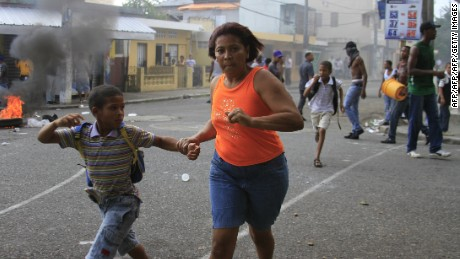A woman and a boy run as the police tries to disperse a few violent demonstrators protesting in the streets of Capotillo neighbourhood in Santo Domingo, against the economic policies of the goverment of President Leonel Fernandez, during a 24-hour strike on July 11, 2011.  AFP PHOTO/ERIKA SANTELICES (Photo credit should read ERIKA SANTELICES/AFP/Getty Images)
