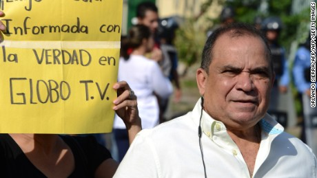 """The director of Globo TV, Honduran journalist David Romero, protests for the closure of the opposition channel, next to a sign reading """"Conatel, I demand to be informed with the truth in Globo TV"""", outside the National Telecommunications Commission (CONATEL) headquarters in Tegucigalpa on May 23, 2016. Protesters accused the government of taking reprisals for the corruption denunciations the channel has done. / AFP / ORLANDO SIERRA        (Photo credit should read ORLANDO SIERRA/AFP/Getty Images)"""