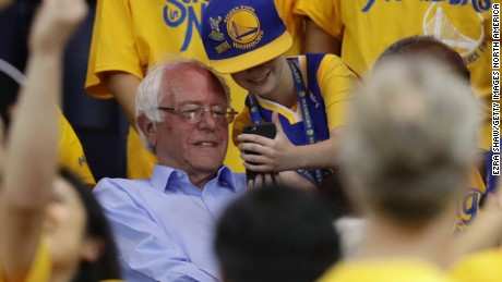 OAKLAND, CA - MAY 30:  Democratic presidential candidate Bernie Sanders takes a photo with a fan at Game Seven of the Western Conference Finals between the Golden State Warriors and the Oklahoma City Thunder during the 2016 NBA Playoffs at ORACLE Arena on May 30, 2016 in Oakland, California. NOTE TO USER: User expressly acknowledges and agrees that, by downloading and or using this photograph, User is consenting to the terms and conditions of the Getty Images License Agreement.  (Photo by Ezra Shaw/Getty Images)