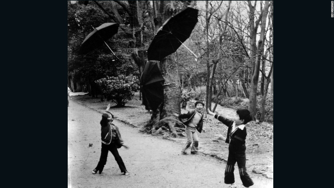Fusayoshi has been documenting Kyoto life since the 1970s. Pictured, three kids in a forest enjoying throwing umbrellas under typhoon winds.