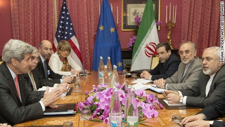 US Secretary of State John Kerry (L) expresses his condolences over the death the of the mother of Iranian President Hassan Rouhani (unseen) before a negotiation session with Iran's Foreign Minister Javad Zarif (R) over Iran's nuclear program in Lausanne March 20, 2015, as European Union Political Director Helga Schmid (4-L) looks on.