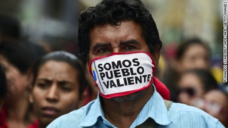 """Supporters of Venezuelan President Nicolas Maduro take part in a protest against the Organization of American States (OAS) and its Secretary General Luis Almagro, in Caracas, on June 01, 2016.  As part of an escalating war of words, Maduro on the eve told the head of the Washington-based organization to """"shove it."""" The verbal barrage came after Almagro called for an urgent meeting on the Venezuelan crisis, warning democracy was at risk in the country.  / AFP / RONALDO SCHEMIDT        (Photo credit should read RONALDO SCHEMIDT/AFP/Getty Images)"""