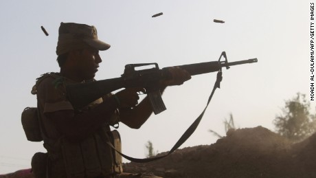 A member of the Iraqi pro-government forces fires his weapon on a front line in the Albu Huwa area south of Falluja on June 1.