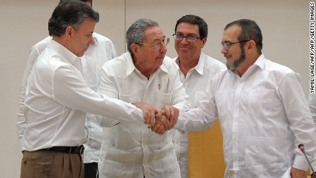 "Colombian President Juan Manuel Santos (L) shakes hands with the head of the FARC guerrilla Timoleon Jimenez, aka Timochenko (R), as Cuban President Raul Castro (C) holds their hands during a meeting in Havana on September 23, 2015. The Colombian government and FARC rebels announced a key breakthrough in their nearly three-year peace talks Wednesday with the signing of a deal on justice for crimes committed during the five-decade conflict. The deal includes the creation of special courts and a broad amnesty, though this will not cover ""crimes against humanity, serious war crimes"" and other offenses including kidnappings, extrajudicial executions and sexual abuse, said officials from Cuba and Norway, the guarantors in the talks. AFP PHOTO / Yamil Lage        (Photo credit should read YAMIL LAGE/AFP/Getty Images)"