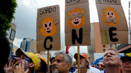 """Opponents to the government of Venezuelan President Nicolas Maduro hold signs reading """"CNE deaf, blind, mute"""" -referring to the National Electoral Council (CNE) as they take part in a demonstration in Caracas on May 14, 2016.   Venezuela braced for protests Saturday after Maduro declared a state of emergency to combat the """"foreign aggression"""" he blamed for an economic crisis that has pushed the country to the brink of collapse. / AFP / FEDERICO PARRA        (Photo credit should read FEDERICO PARRA/AFP/Getty Images)"""