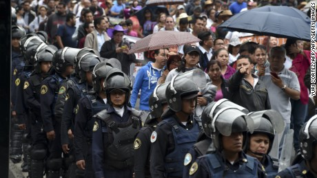 Riot police stand guard during a teachers protest in Mexico City on June 3, 2016.  The teachers' union opposes an educational reform enacted by the government of Mexican President Enrique Pena Nieto in 2013. / AFP / YURI CORTEZ        (Photo credit should read YURI CORTEZ/AFP/Getty Images)