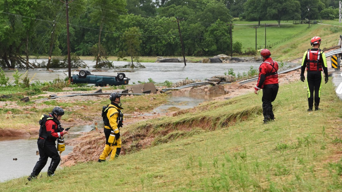 """Rescue crews search for a missing man near Brenham, Texas, on Friday, May 27. The man's truck, seen in the background, was found flipped over along Rocky Creek. At least seven people <a href=""""http://www.cnn.com/2016/05/29/us/flooding-texas-kansas/"""" target=""""_blank"""">died in flood-related incidents</a> after the region was inundated with rain, authorities said."""