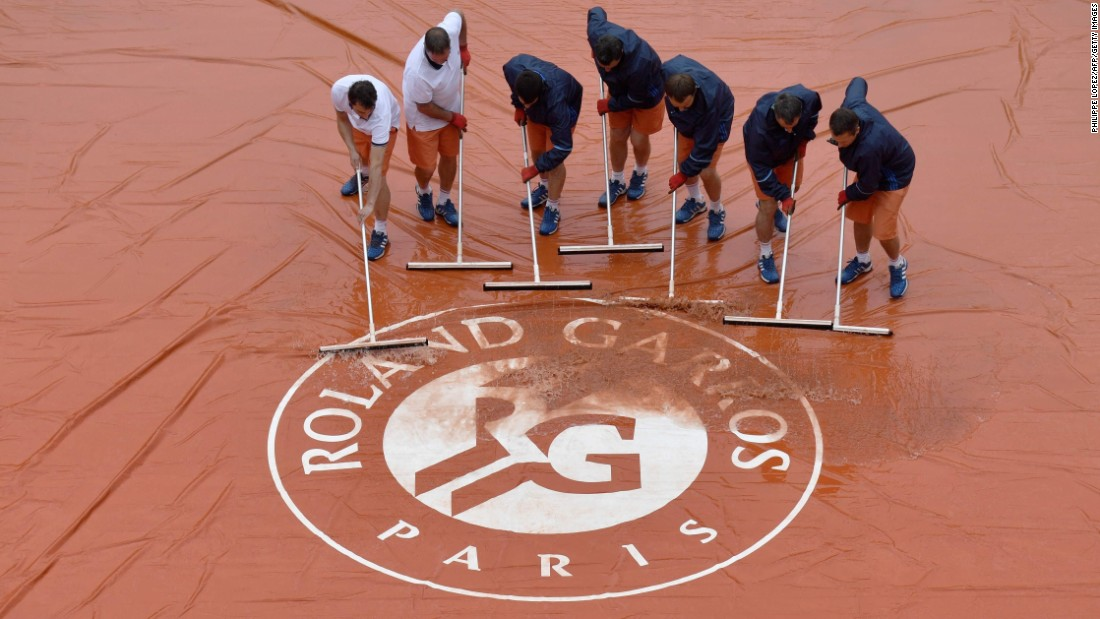 Workers at the French Open tennis tournament sweep a court's tarp on Saturday, May 28.